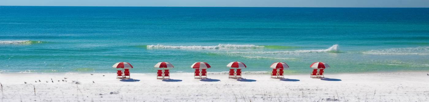 Beach Scene with Red Chairs and Red Umbrellas